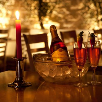 two glasses of champagne on the right in the middle a bottle of champagne in ice and a lit red candle on the left